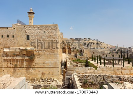 Minaret of Al-Aqsa Mosque surrounded by walls and ancient ruins in Old City of Jerusalem, Israel. - stock photo