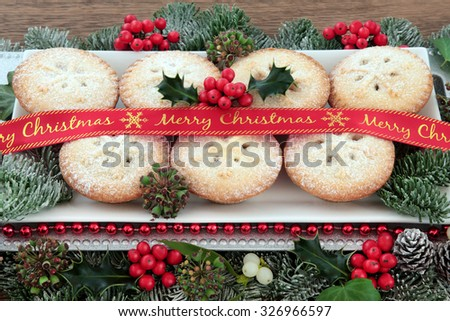 Mince pie cakes on a plate with red merry christmas ribbon, holly, mistletoe and winter greenery.  - stock photo