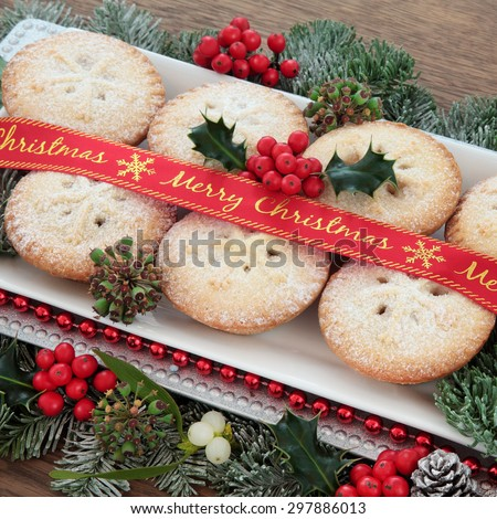 Mince pie cakes with merry christmas ribbon, holly, mistletoe and winter greenery over white background. - stock photo