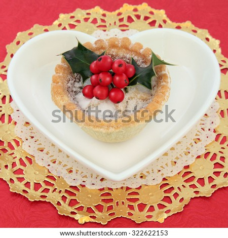 Mince pie fruitcake and holly on a gold doilie on a heart shaped plate over red background. - stock photo