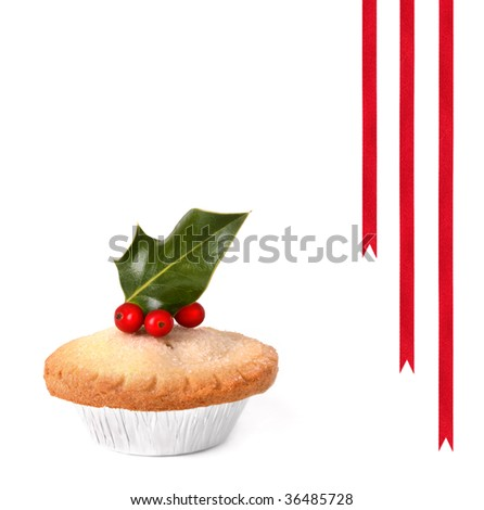 Mince pie topped with holly leaves with red berries, over white background with three red ribbons. - stock photo