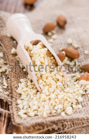 Minced Almonds (detailed close-up shot) on dark wooden background - stock photo