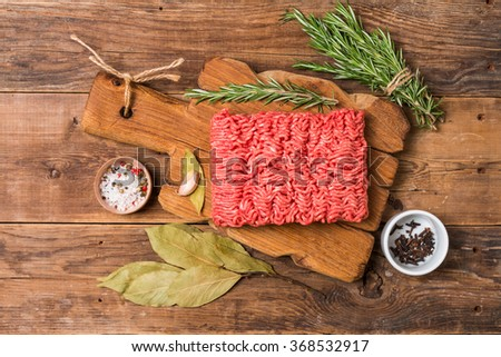 Minced meat on cutting board with seasoning and fresh rosemary on wooden background, top view - stock photo