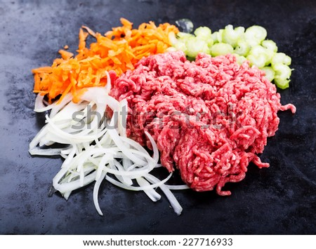 minced meat with fresh vegetables on black background - stock photo