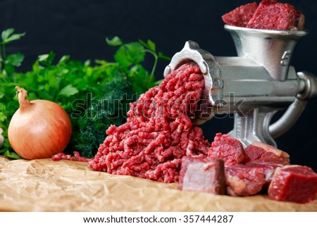 Mincer with fresh minced beef meat with vegetable - stock photo