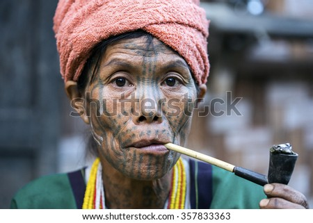 MINDAT, MYANMAR - DECEMBER 7: Chin tribe tattoed woman (Muun) poses for a photo on December 7, 2015 Mindat, Myanmar. Chin people, also known as the Kukis are a number of Tibeto-Burman tribal people. - stock photo