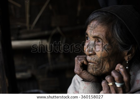 MINDAT, MYANMAR - DECEMBER 8: Chin tribe tattooed woman (Muun) poses for a photo on December 8, 2015 Mindat, Myanmar. Chin people, also known as the Kukis are a number of Tibeto-Burman tribal people. - stock photo