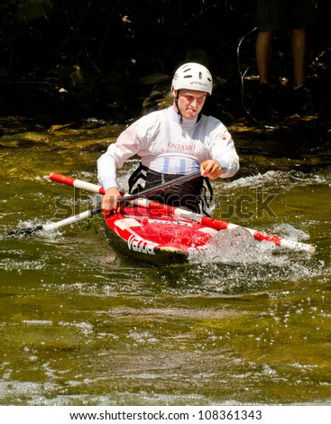 MINDEN, ONTARIO - JULY 21: An unidentified kayaker transports a replacement slalom gate pole at Ontario Summer Race 2012 on July 21, 2012 at Gull River in Minden, Ontario, Canada. - stock photo