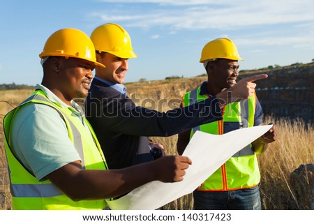 mine manager and workers at quarry discussing future plan - stock photo