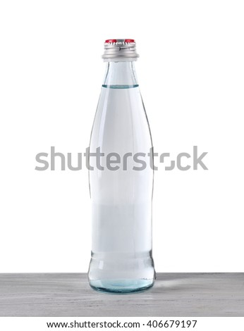 Mineral water in glass bottle on wooden table on grey background - stock photo