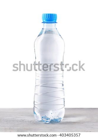 Mineral water in plastic bottle on wooden table on grey background - stock photo