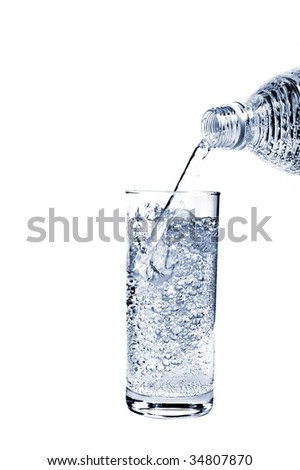 Mineral water pouring from bottle into a glass - stock photo