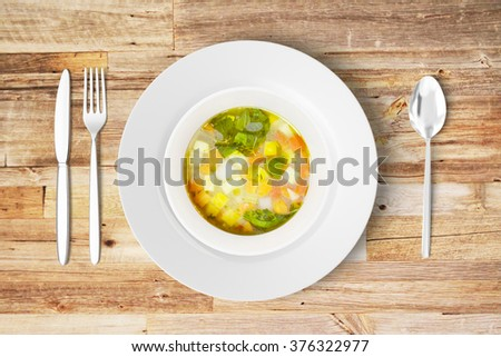 Minestrone soup in white plate with knife, fork and spoon on wooden table - stock photo