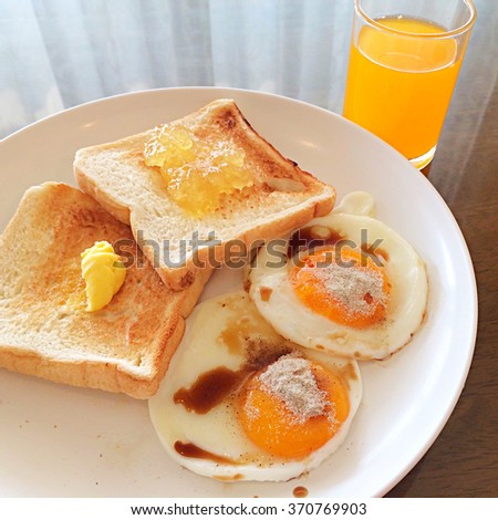 Mini bar breakfast with eggs bread and orange juice and a little bit butter - stock photo