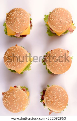 Mini beef burgers from above on white background with shadows - stock photo