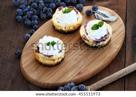 Mini blueberry cheesecakes with whipped cream surrounded by fresh berries. Extreme shallow depth of field with selective focus on dessert in front of image. - stock photo