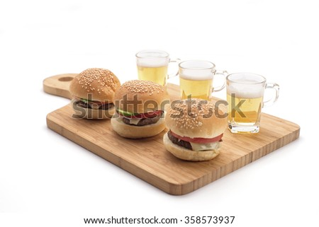 Mini burgers and and beer shots on a wooden serving board isolated on white. Party food. - stock photo