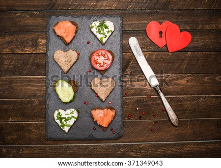 Mini canapes heart shape with different toppings on black slate board, vintage knife and two red hearts on rustic wooden background. Delicious appetizers. Valentines day food. - stock photo
