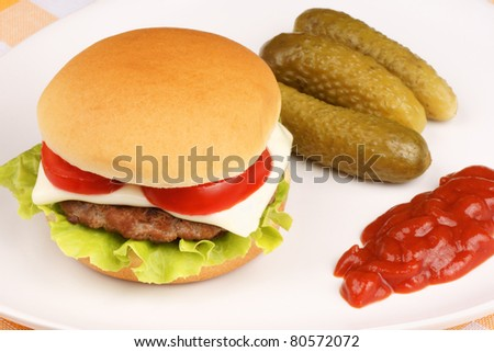 Mini cheese burger with tomato and lettuce and some pickles and ketchup on a white dish. - stock photo