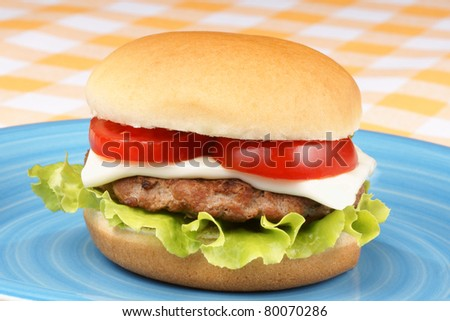 Mini cheese burger with tomato and salad on a blue dish - stock photo