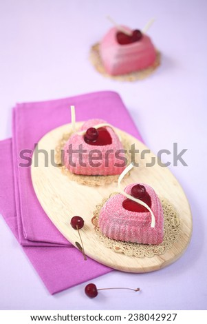 Mini Cherry Mousse Heart Cakes on a wooden cutting board, purple napkin and light purple background. - stock photo