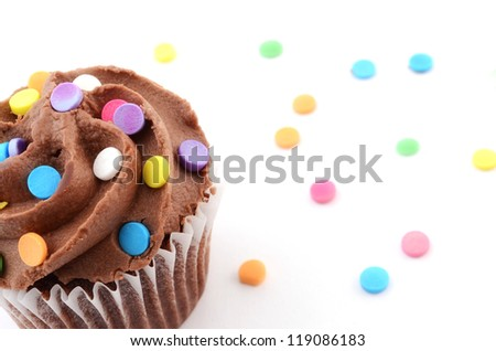 Mini chocolate cupcake with colorful sprinkles on white background - stock photo