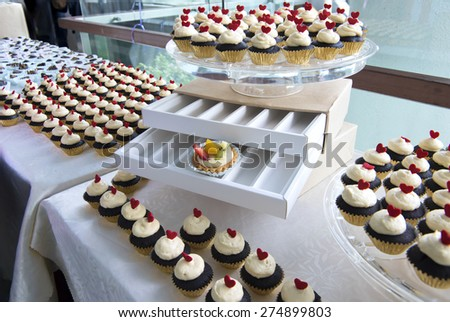 Mini cupcake with red heart shaped topping.  The desserts are arranged and displayed in desserts bar at a opened cocktail party. - stock photo