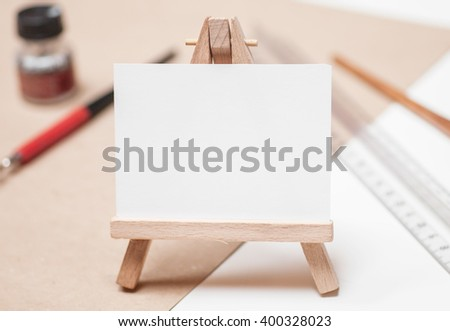 mini easel with canvas on table with pen, ink, ruler on white table - stock photo