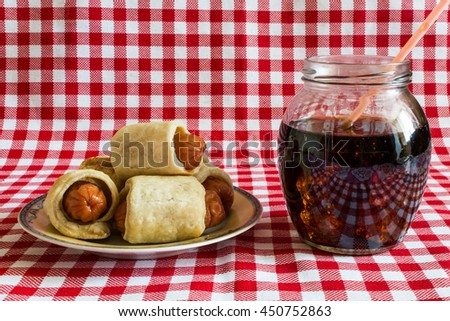 Mini hot dog homemade -  (sausage in pastry) with cola on a plaid background. In Europe, the sausage in pastry served with different sauces, eat them with a fork. - stock photo