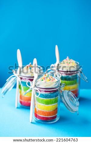 Mini jars of rainbow cake - stock photo