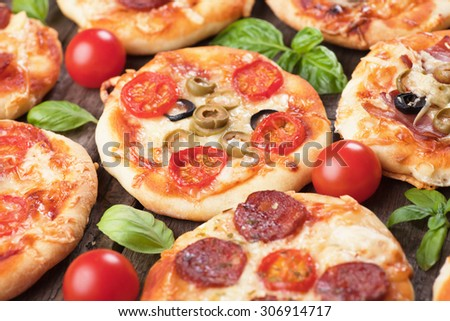 Mini margarita pizzas with cherry tomato, cheese and olives - stock photo
