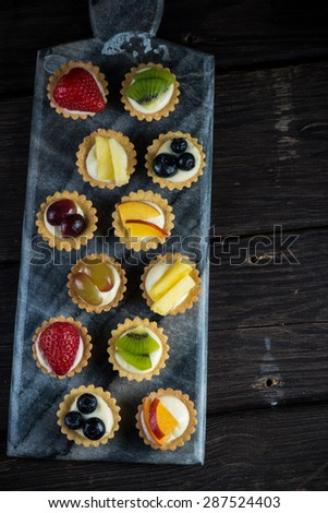Mini pastry tartlets with fresh fruits, on marble serving board - stock photo