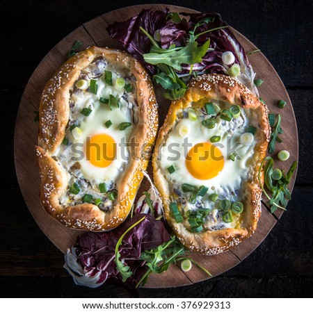 Mini pizza with fried egg on wooden board - stock photo