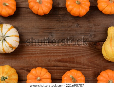 Mini pumpkins and gourds forming a frame with a blank middle, Horizontal format on a rustic wood background. - stock photo