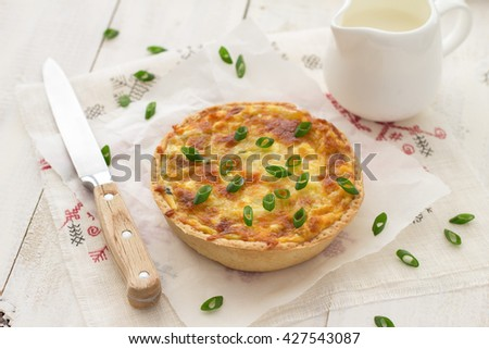 Mini quiche with green onions and cheese on a light wooden background - stock photo