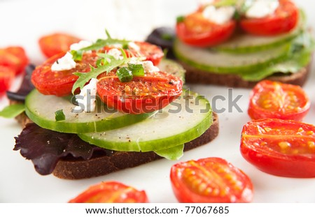 Mini Sandwiches with Broiled Tomatoes, Cucumbers, Greens and Goat Cheese - stock photo