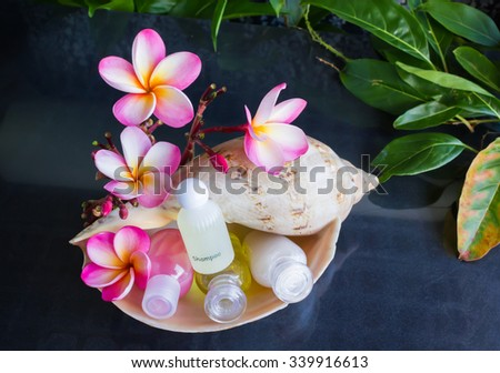Mini set of bubble bath and shower gel in sea conch shell  decorated with beautiful flower plumeria  - stock photo