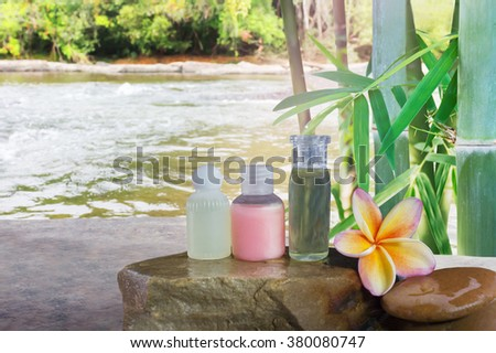 Mini set of bubble bath and shower gel liquid and frangipani flower on pebble rock and green nature relaxing spa  feeling with green bamboo tree background - stock photo