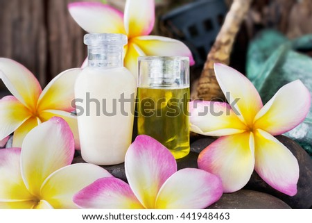 Mini set of bubble bath and shower gel liquid with pink flowers plumeria or frangipani on timber or log wooden background,shampoo and conditioner spa treatment - stock photo
