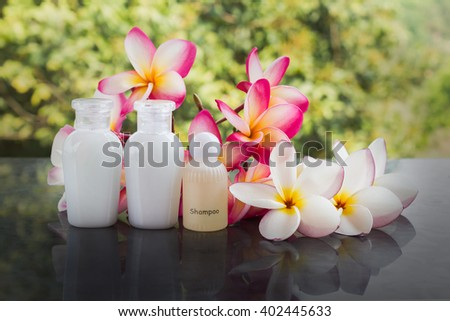 Mini set of bubble bath and shower gel liquid with pink white flower on green nature relaxing feeling background - stock photo