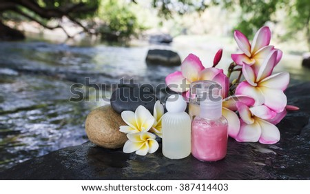 Mini set of bubble bath shower gel liquid with flowers and pebble on waterfall rock  with natural water relaxing feeling background and copy sapce - stock photo