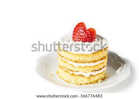 MIni sponge cake with cream and strawberries for Valentines day on white plate. Selective focus. - stock photo