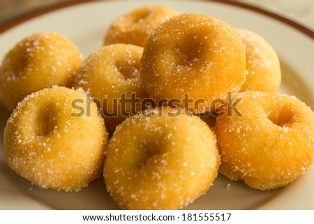 Mini sugar coated doughnuts piled on  plate,hight calorie - stock photo