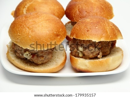 Mini Turkey Burger Plate Four mini blue cheese turkey burgers on buns.  The turkey slammers are on a white plate with a white background. - stock photo