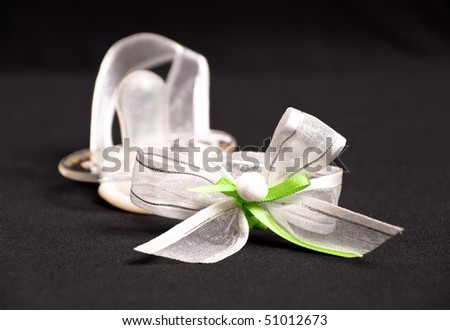 Miniature Baby Pacifier Asset on Ribbon - stock photo