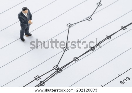 miniature businessman standing on the compare graph - stock photo