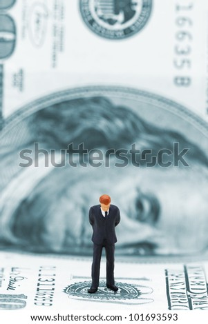 Miniature businessman thinking on dollar banknote. Financial crisis concept. - stock photo