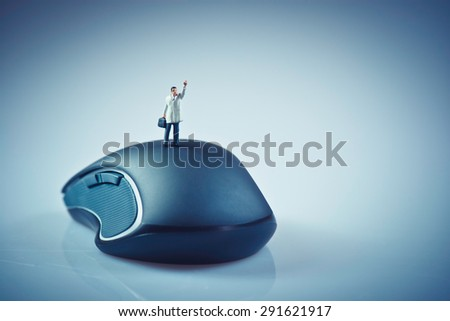 Miniature businessman waving on top of computer mouse. Business concept. Macro photo - stock photo