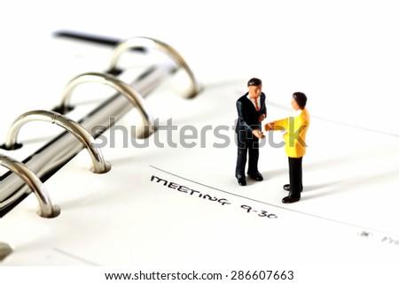 Miniature businessmen filofax - stock photo
