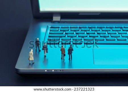 Miniature businessmen walking over the laptop - stock photo